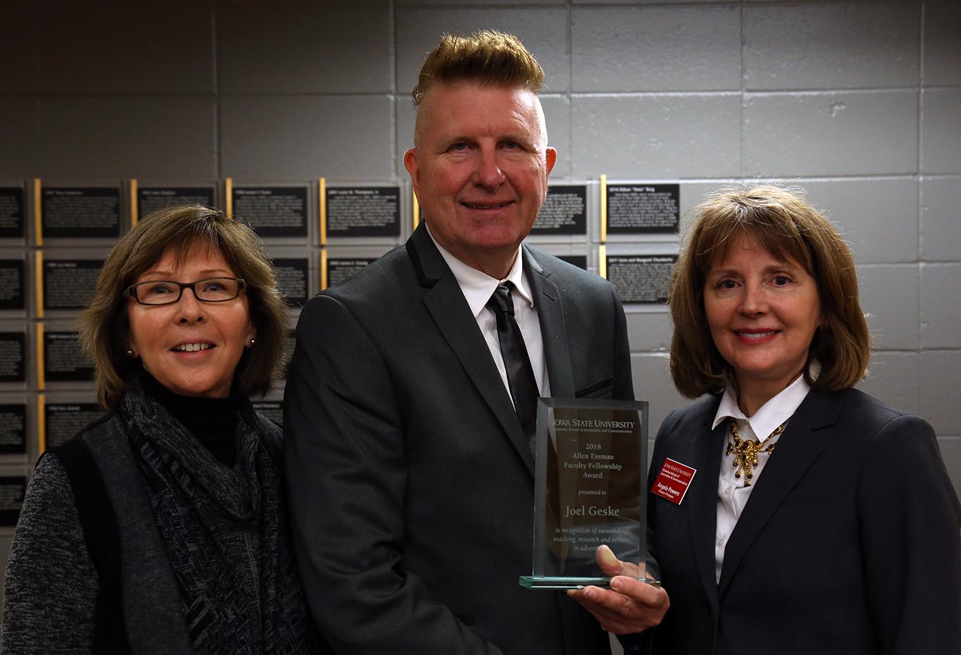 Denise Essman, Joel Geske and Angela Powers stand with plaque