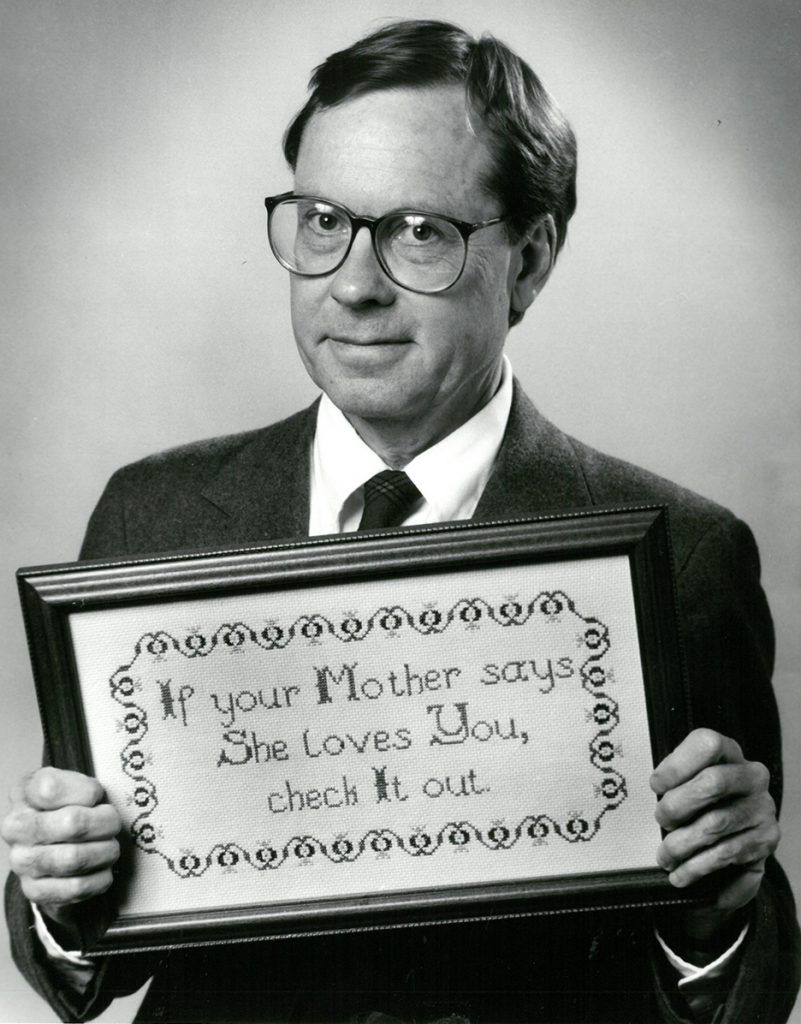 """Giles Fowler with cross-stitch saying, """"If your Mother says she loves you, check it out."""""""