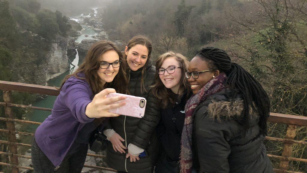 students take selfie on bridge in Italy
